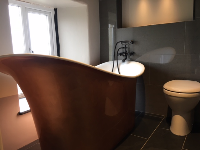 Stunning country bathroom with a copper bath finished on slate flooring and wall cladding