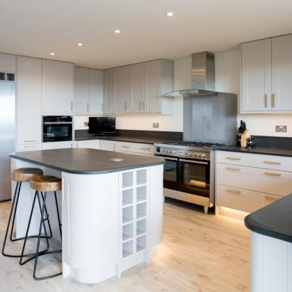 Large double range oven and a kitchen island, both with natural stone work tops