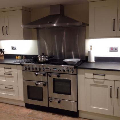 Range oven surrounded by slate worktops in a modern kitchen