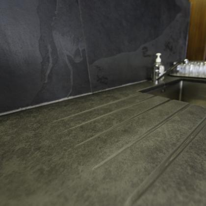 Commercial worktop for a kitchen sink surround with drainage grooves