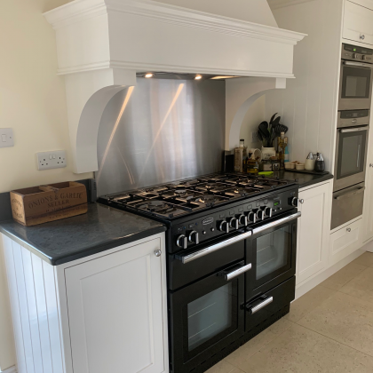 Insert range cooker in a white kitchen with hood over and slate surrounds