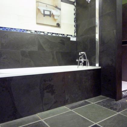 Traditional bath with slate wall tiles surrounding the bath and slate floor tiles.
