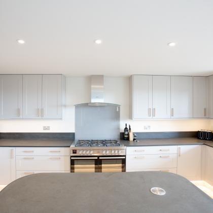 Stunning white kitchen with central breakfast bar and slate worktops