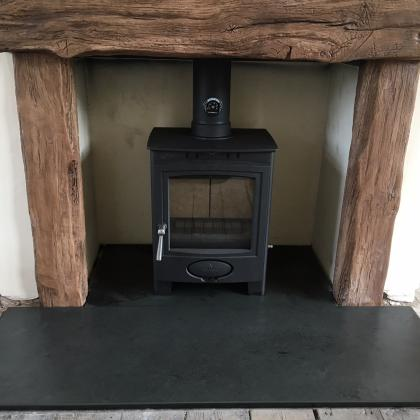 Black slate traditional fire hearth with a woodnurner