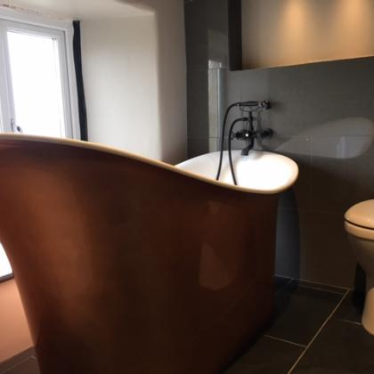 Superb modern large copper bath with slate flooring