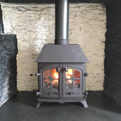 Lit fire in a woodburner in a traditional inglenook fireplace