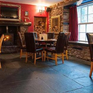 Restaurant seats by the fire with natural slate slabs