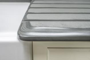 Polished grooves on slate draining board leading into recessed sink
