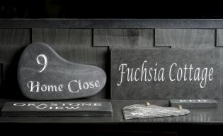 A collection of slate signs for houses with numbers