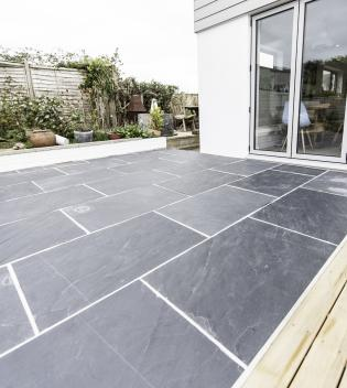 Slate flagstones in a patio below French doors, hard wearing with a rough finish.