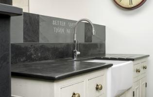Belfast sink recessed into wooden custom made unit with hand cut slate kitchen worktop