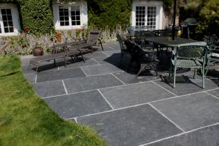 Slate flagstones that are hand split and laid in a traditional cottage garden