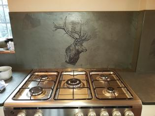 Engraved sign with a stag behind a cooker.