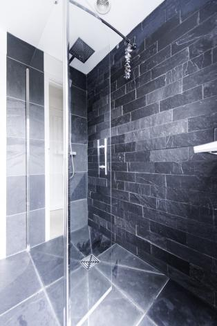 Flooring and wall tiles in a shower room with glass door