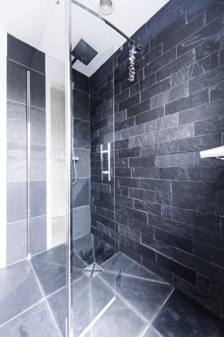 Glass shower with stunning polished natural stone wall tiles