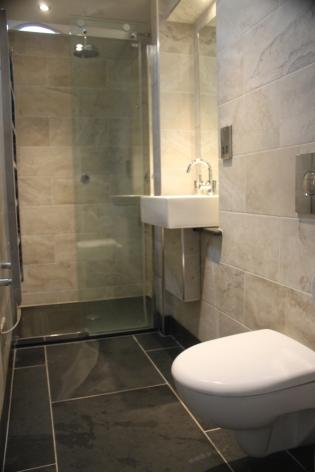 Slate shower tray with travertine wall tiles and natural slate tray.