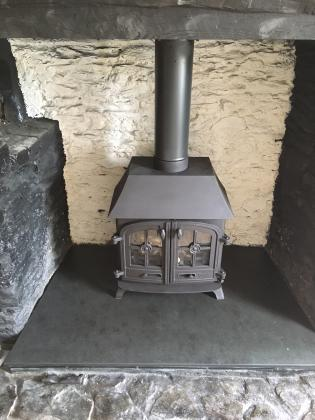 Cottage style woodbruner with a slate fire hearth